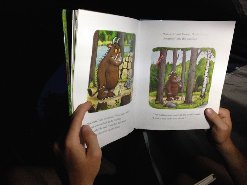 family reading in tent gruffalo book