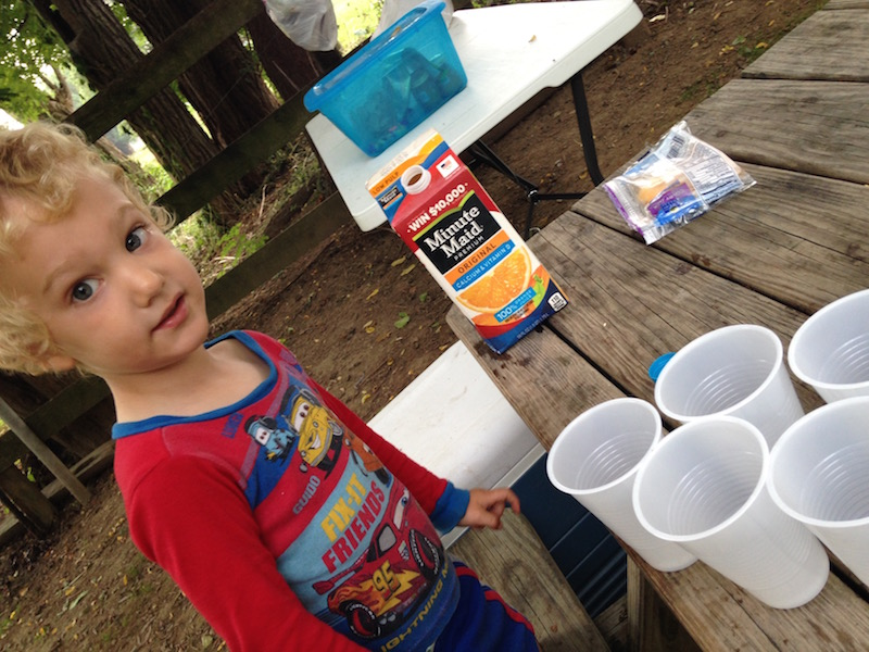 first camping trip with kids getting them involved pouring drink